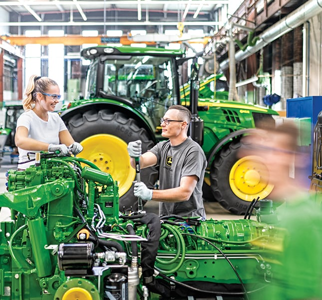 At the John Deere Factory in Mannheim, Germany, a man and woman are working together on the tractor line.