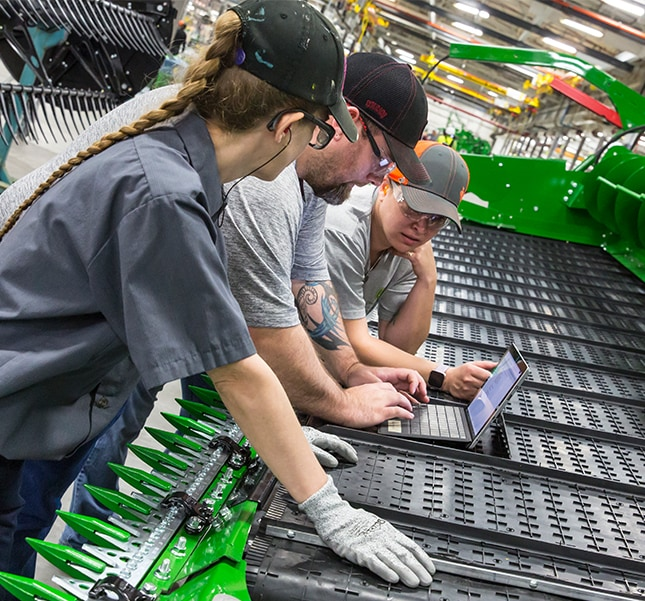 Three John Deere employees looking at a laptop that is sitting on a combine head at the Harvester Works factory in East Moline, Illinois, United States.