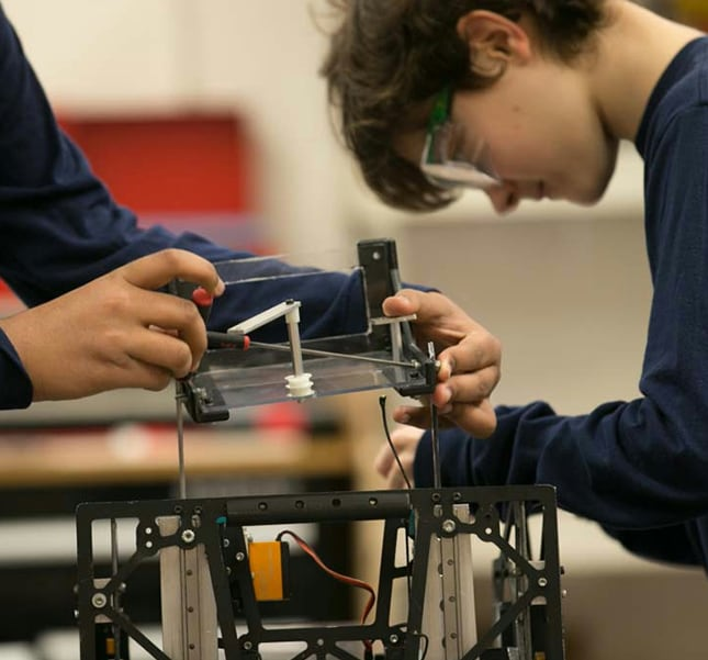 Close up of an engineering student building a robotic device with another student behind her building his device.