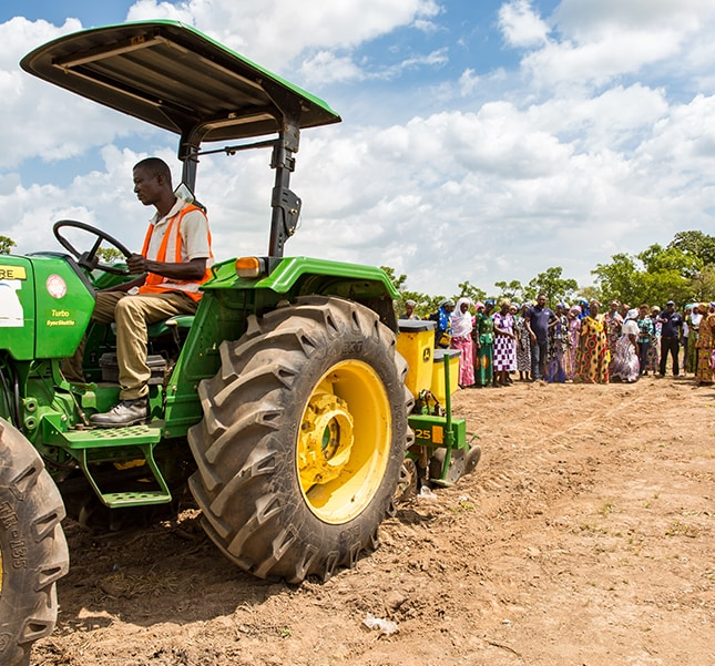 Women farmers watching how a John Deere tractor and planter is used in northern Ghana.