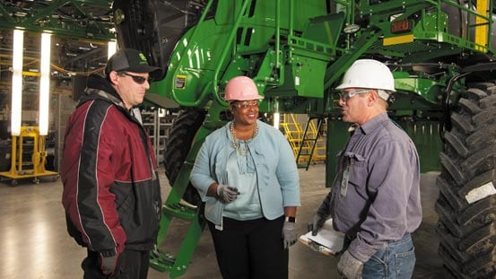 Three people with hardhats talking in factory setting