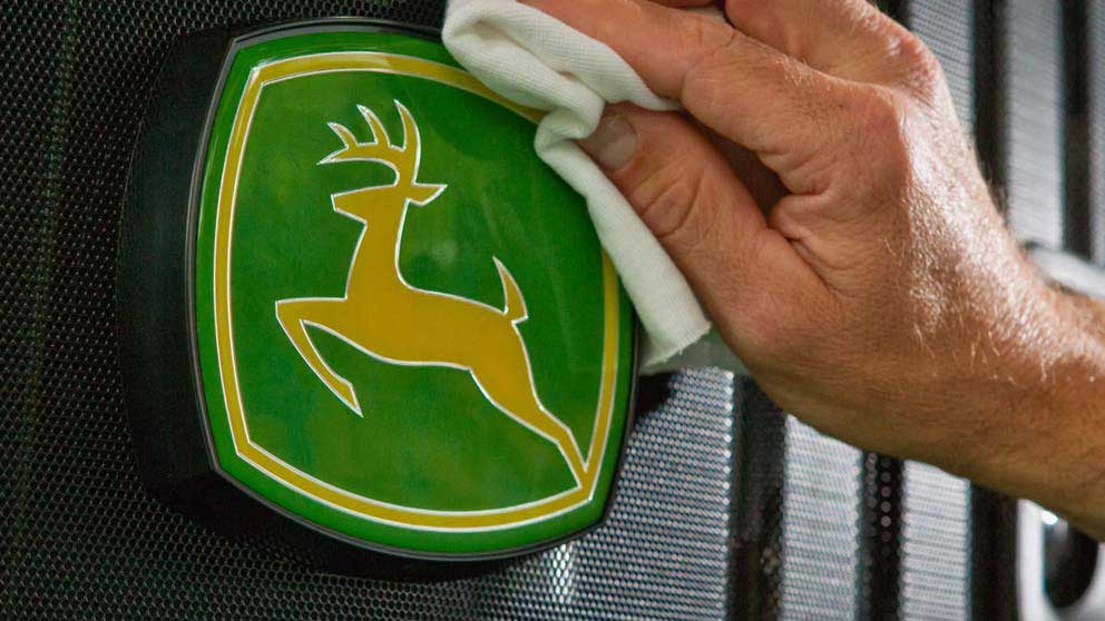 Man's hand polishes a John Deere logo with a cloth.