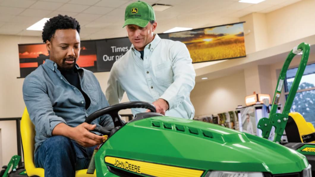 a Deere Dealer talking to a man on a mower