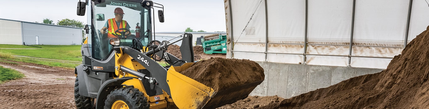 244L compact front end loader scoops a bucket full of dirt from a large pile