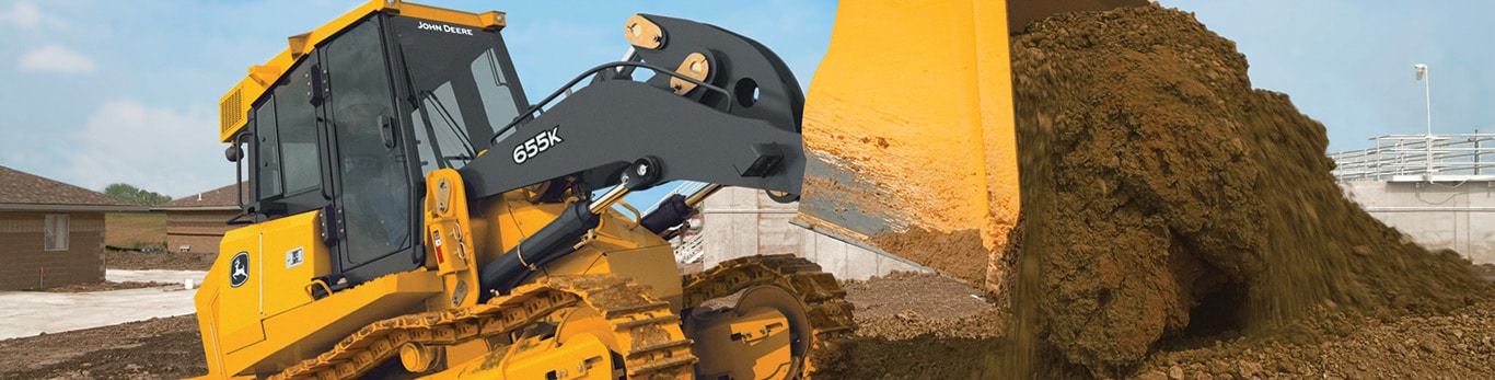 John Deere 655K Crawler Loader dumping a load of dirt on a job site.
