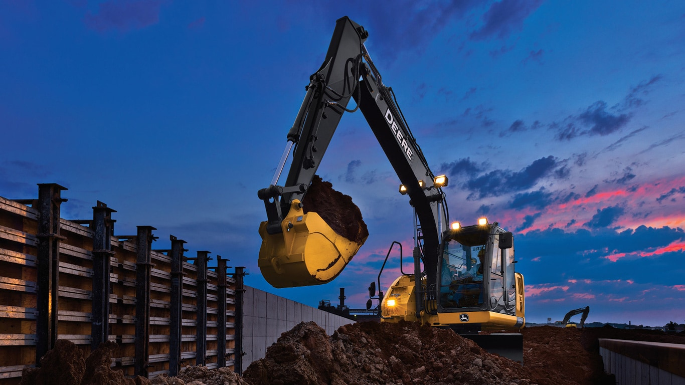135G Mid-Size Tracked Excavator moving dirt with the headlights on at sunset