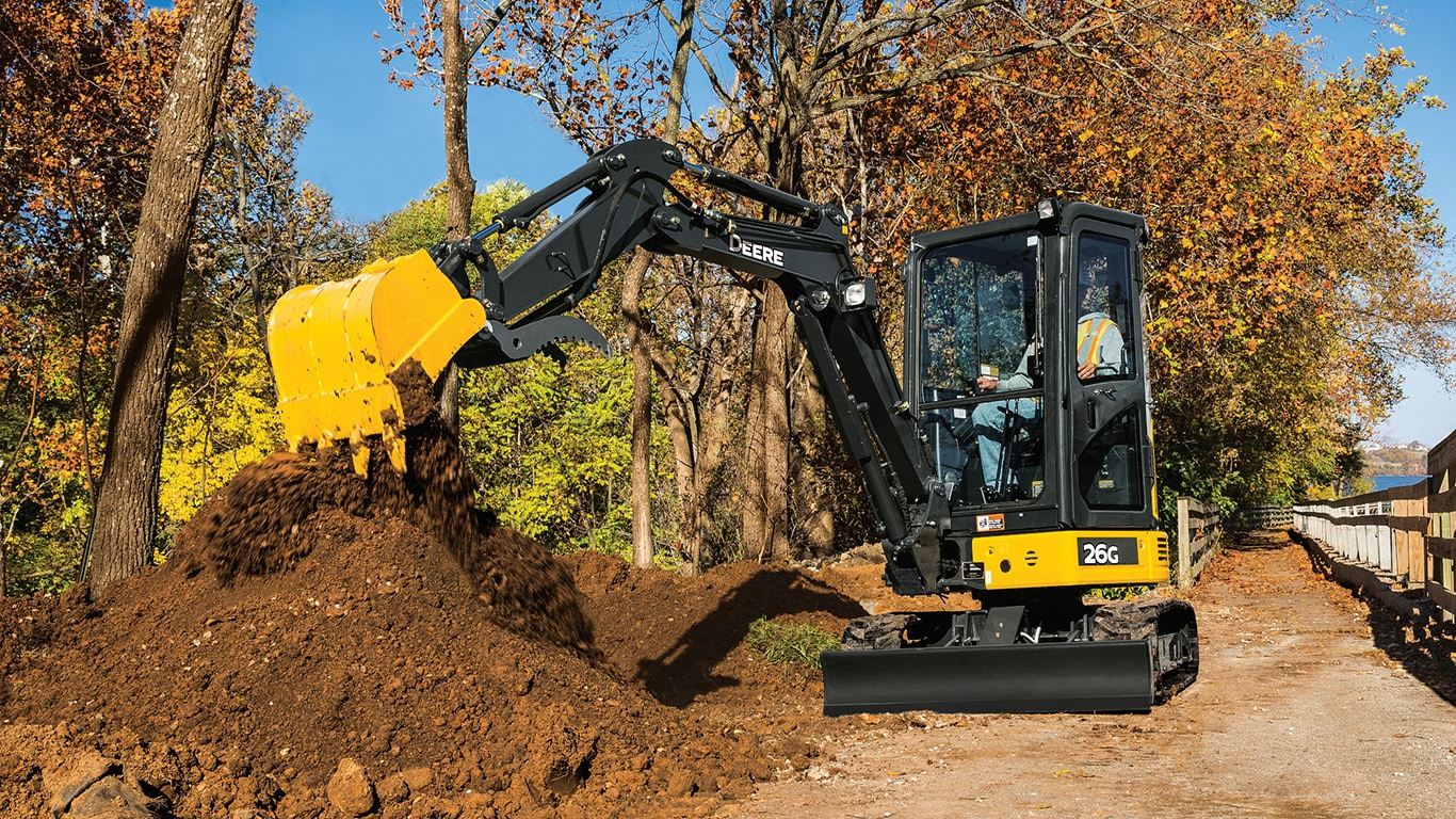 26G John Deere mini tracked excavator moving dirt at a work site.