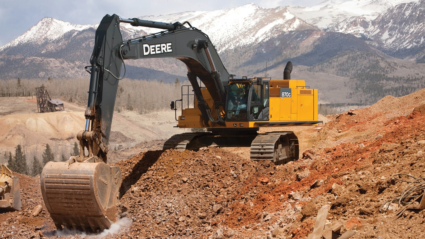 John Deere's biggest excavator, the 870G, breaking ground with mountains in the background