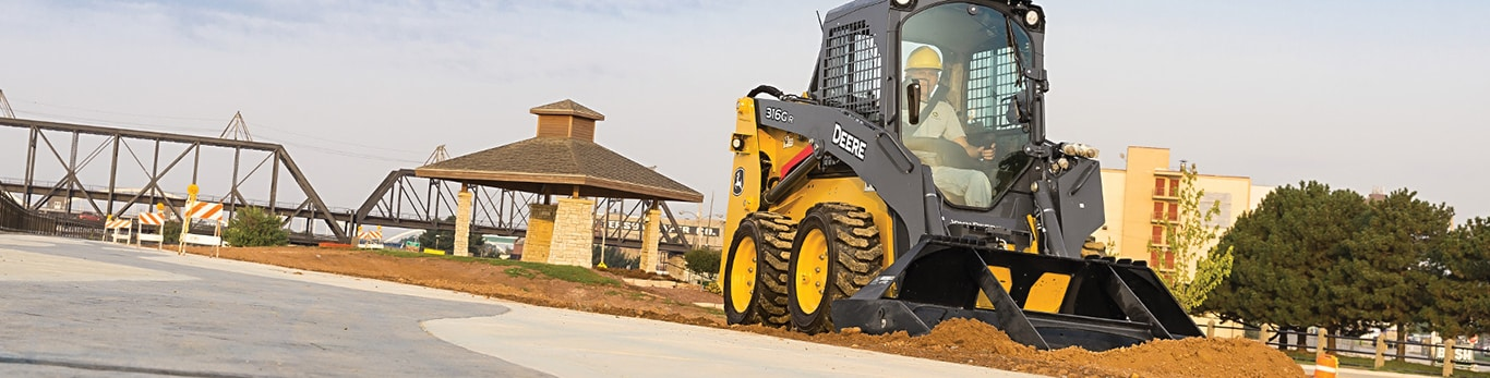 skid steer with landplane attachment on a jobsite in a park