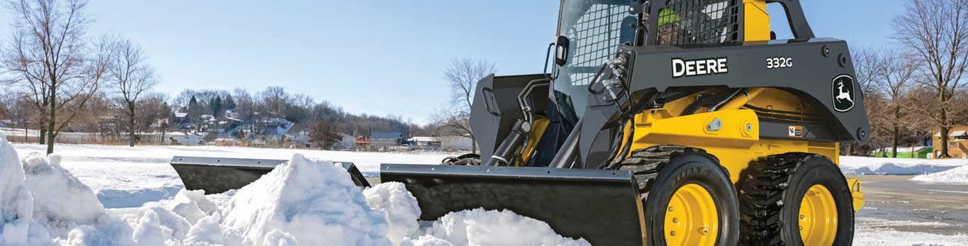 332G Large Skid Steer pushes snow in a parking lot with a V blade attachment