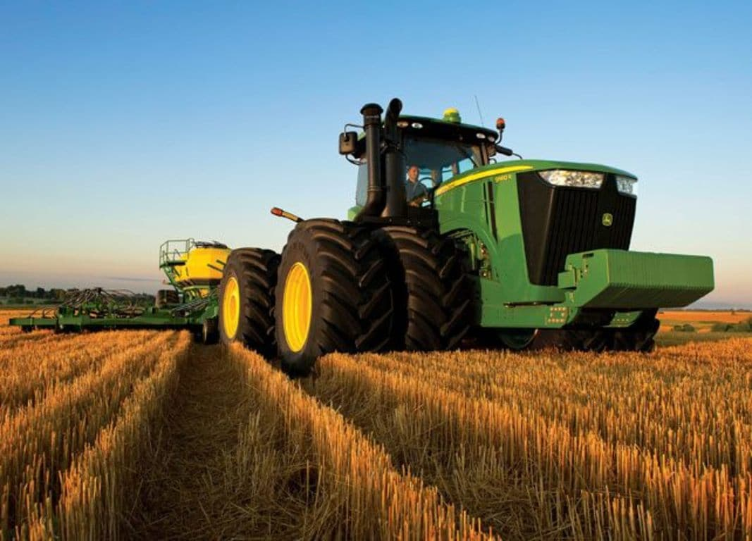 A 9560R tractor driving through a field.