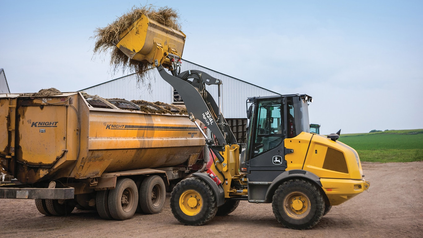 324L John Deere Compact Wheel Loader unloading hay using the high-lift option