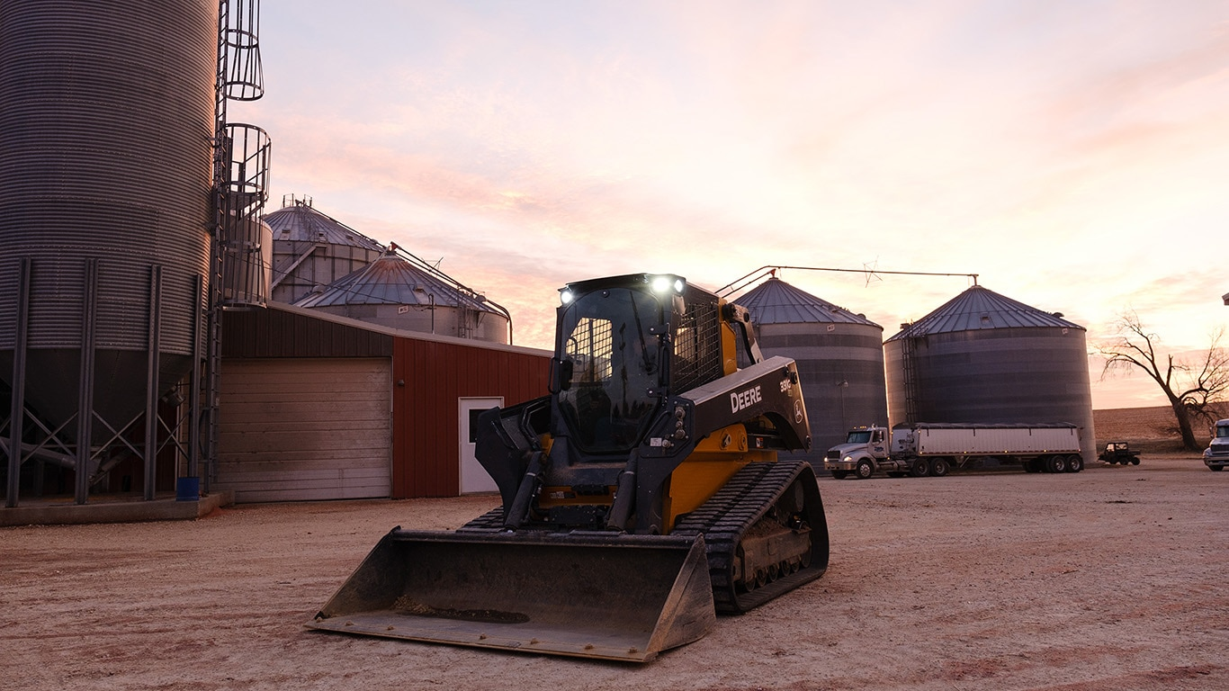 331G Compact Track Loader parked in front of farm bins and a storage shed with a sunset in the background.