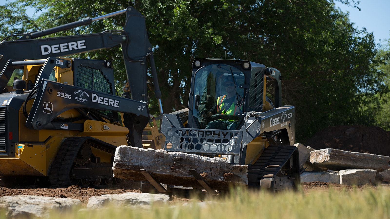 Compact track loaders haul large landscaping rocks