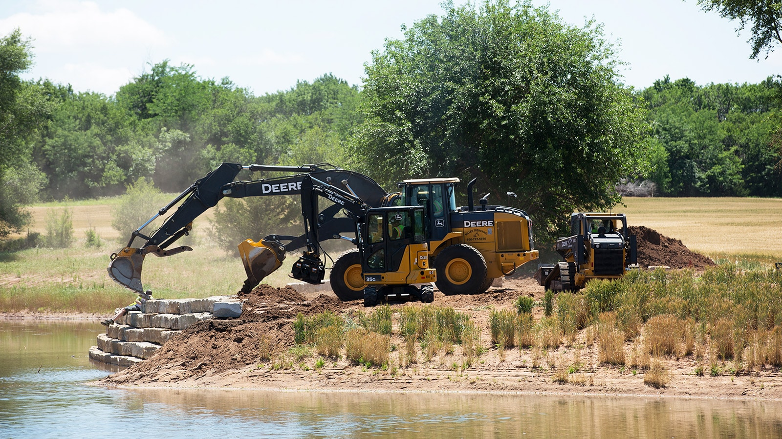 Wheel loader, excavators and compact track loaders work on a retaining wall by a pond.