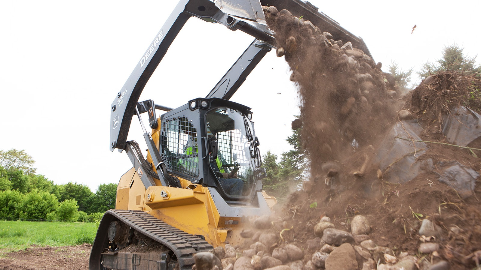 333G Compact track loader unloads a bucket of dirt