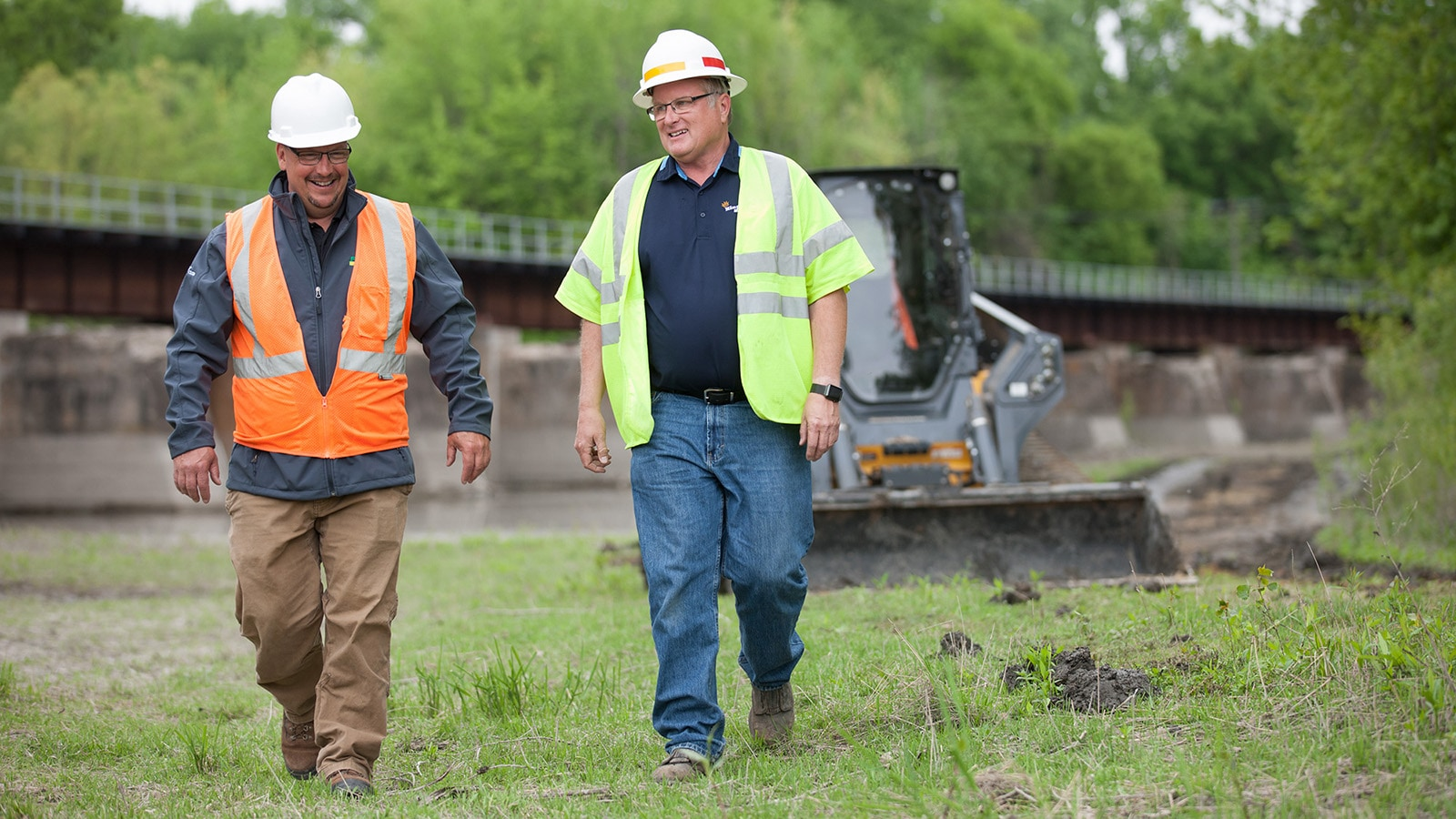 Bruce Speirs and Bill King walk through grass in front of a bridge and skid steer.