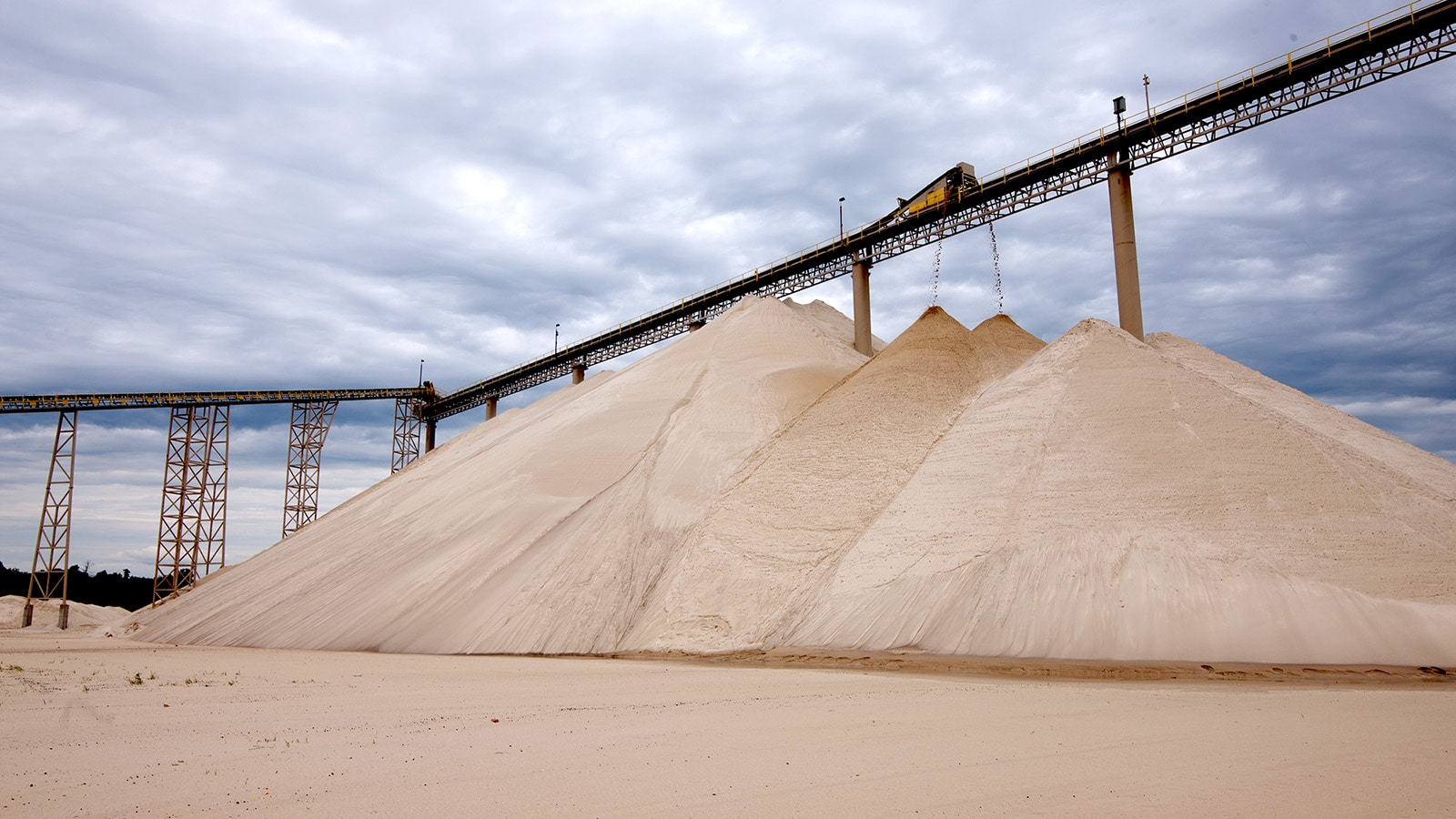 A conveyer drops loads onto already massive piles of sand
