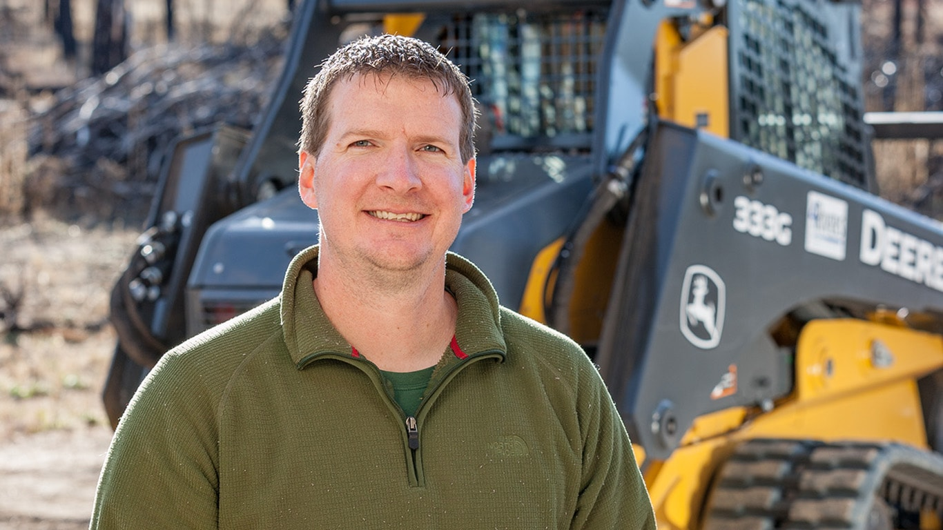 Neil Behnke stands in the forest in front of his 333G Compact Track Loader