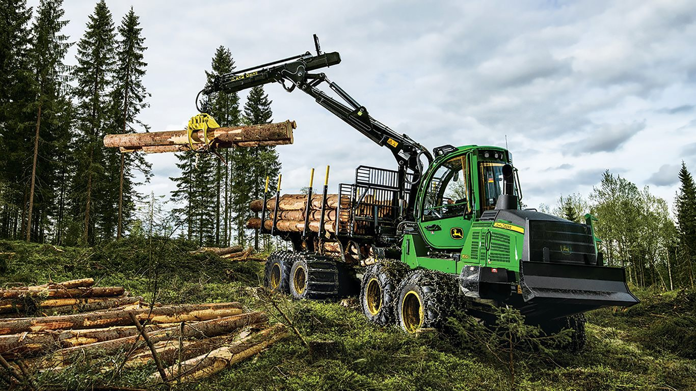 1510G Forwarder loads a log from a pile in the woods onto the forwarder rack