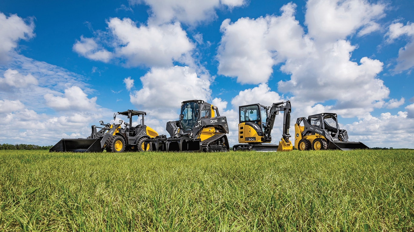 Line-up of compact construction equipment in a grassy field with blue sky in the background
