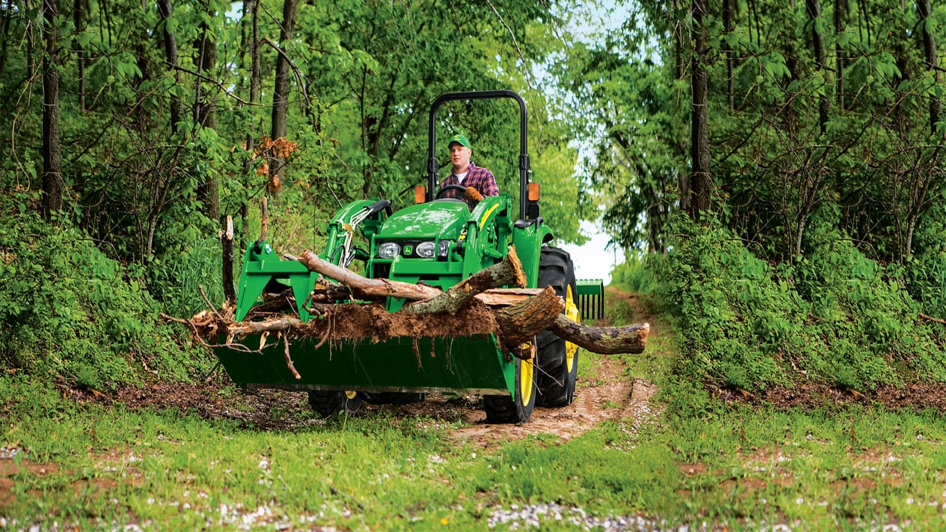 Man in woods driving tractor hauling tree limbs