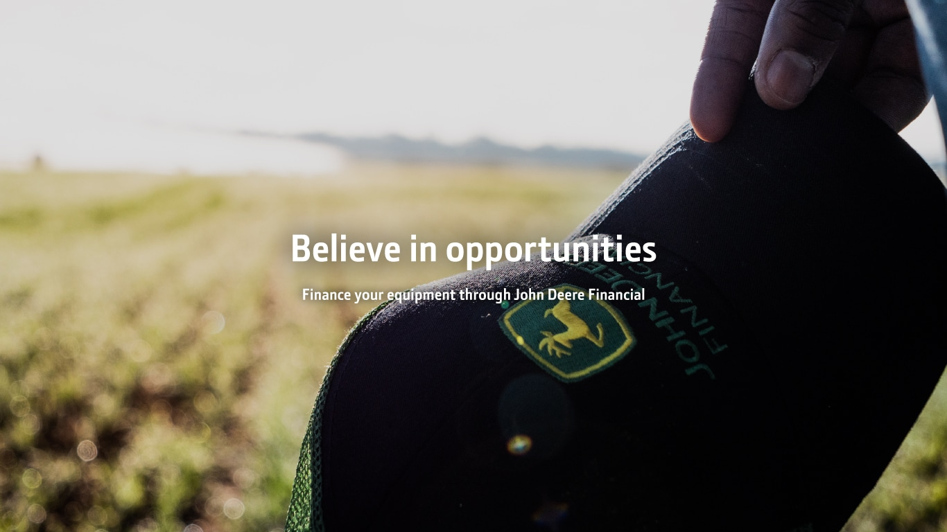 Image of a laptop, John Deere Financial coffee cup and John Deere hat.