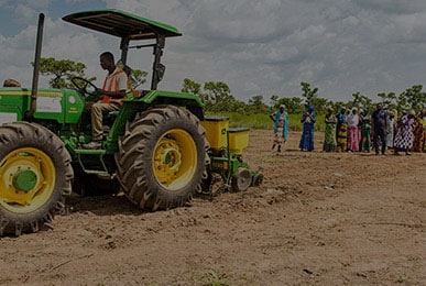 Villagers watching a tractor working in Ghana, Africa