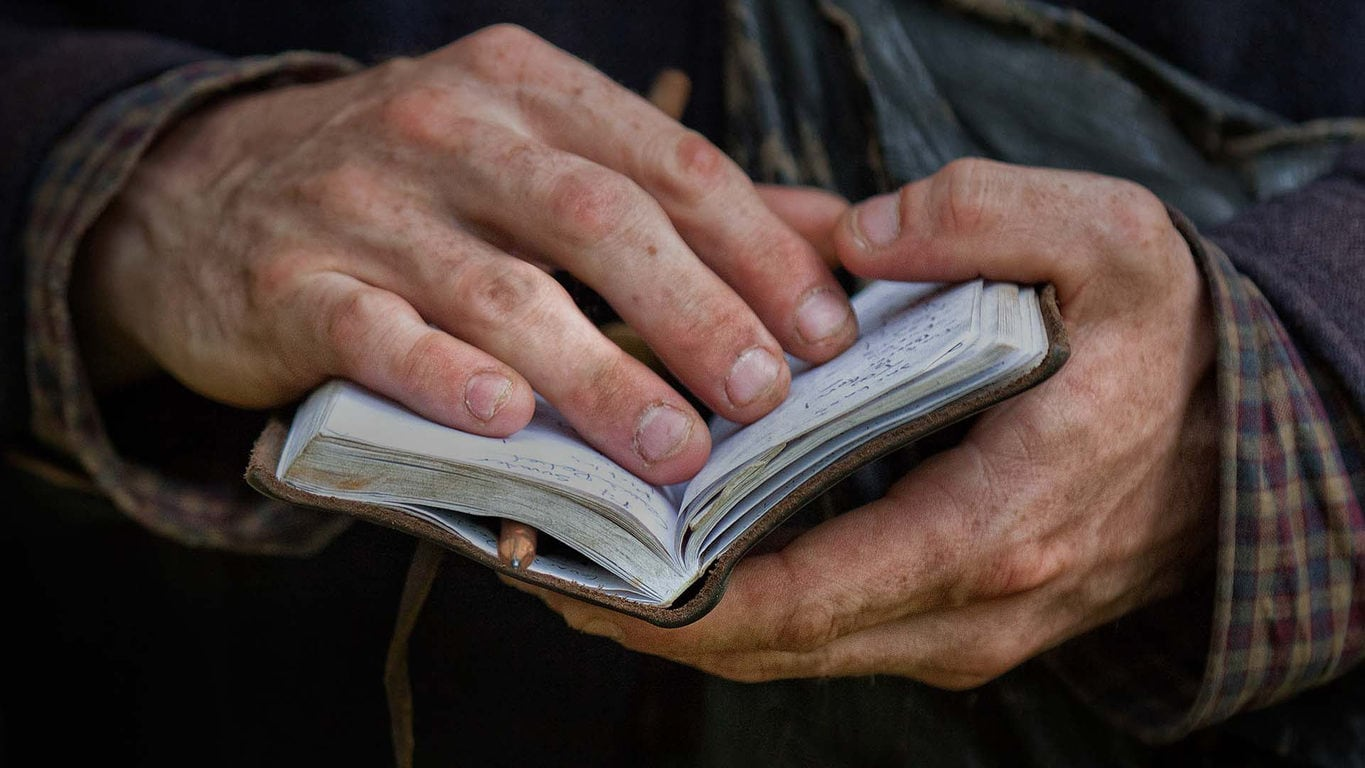 dirty hands flipping through a notebook