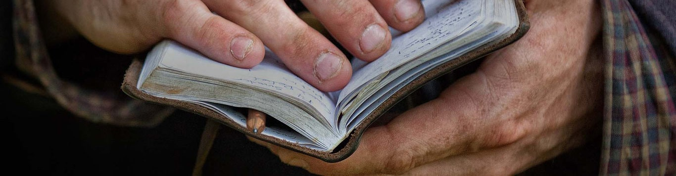 Close up on dirty hands holding notebook