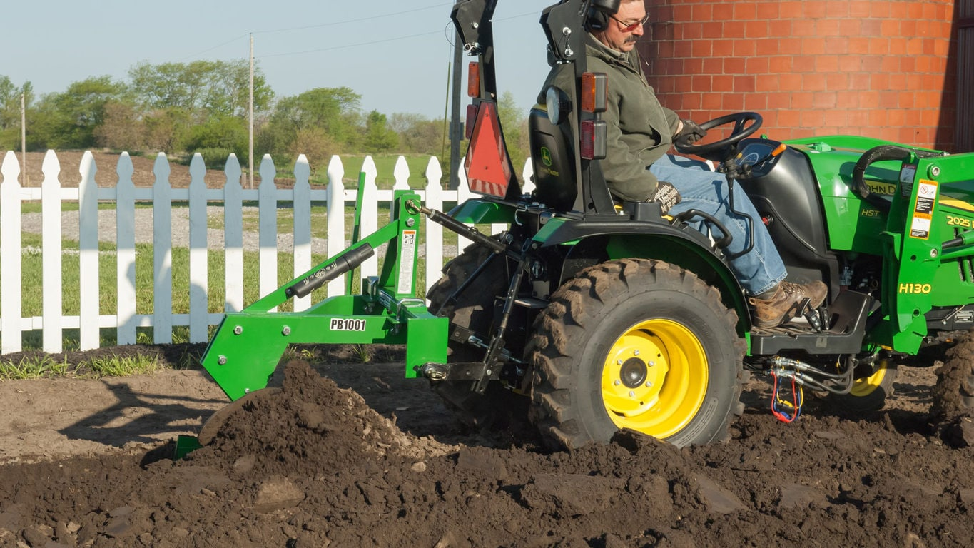 man plowing dirt with plow attachment on a tractor