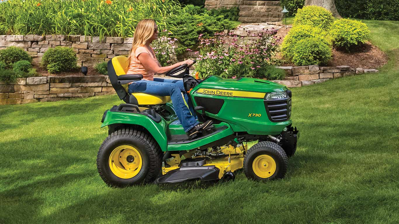 Woman on X700 series tractor on a residential lawn