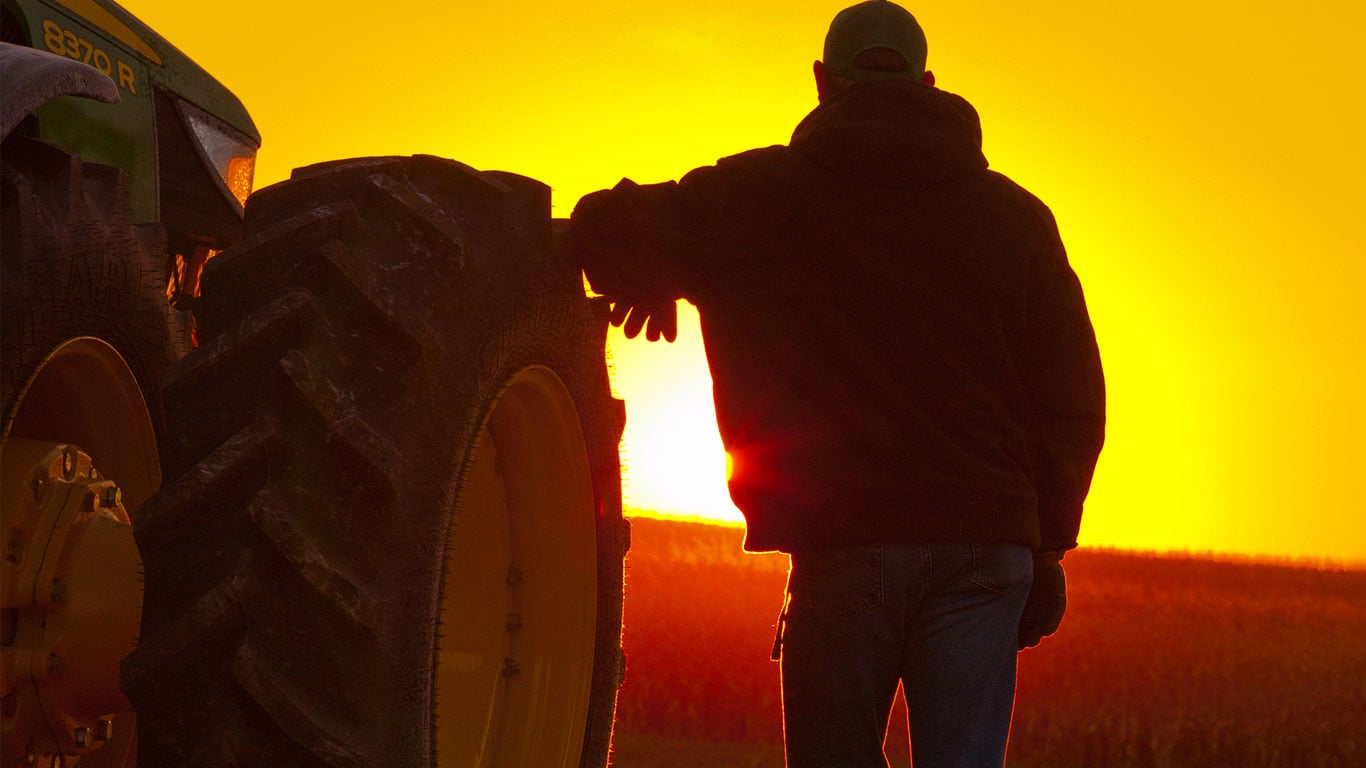 man and tractor in sunset