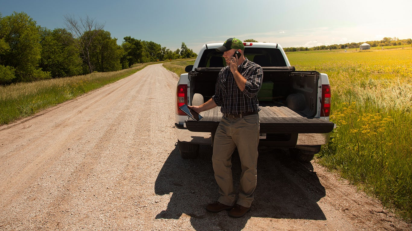 Man using his phone and tablet, standing behind his truck on a country road.