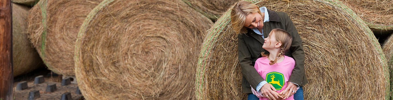 Image of a woman and a girl in front of round hay bales.