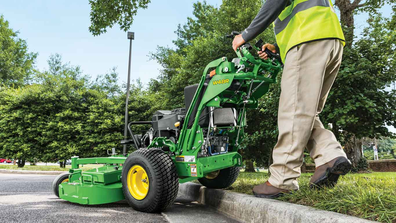 Landscaper going over a curb with a John Deere W48R Commercial Walk Behind Mower