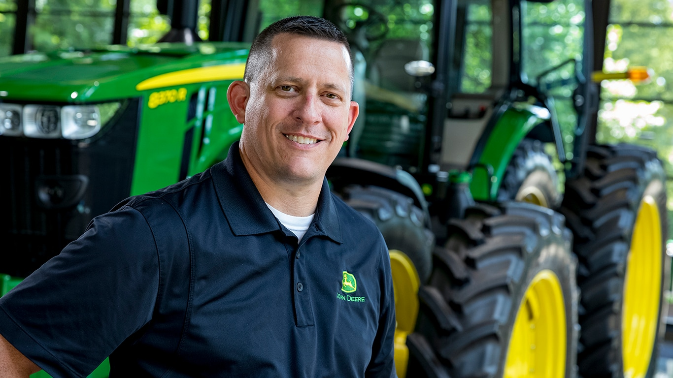 Military veteran standing proudly in front of a John Deere tractor