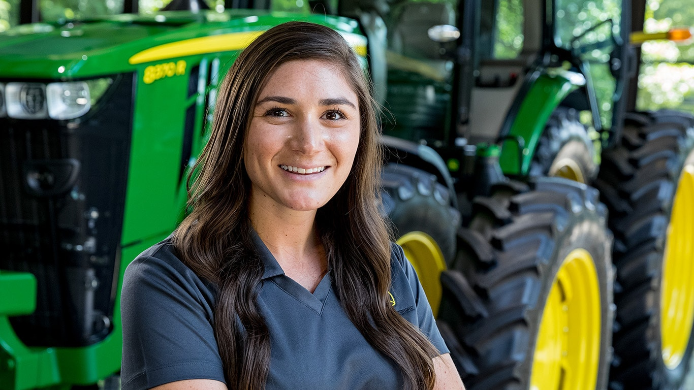 Female employee standing proudly with a John Deere tractor