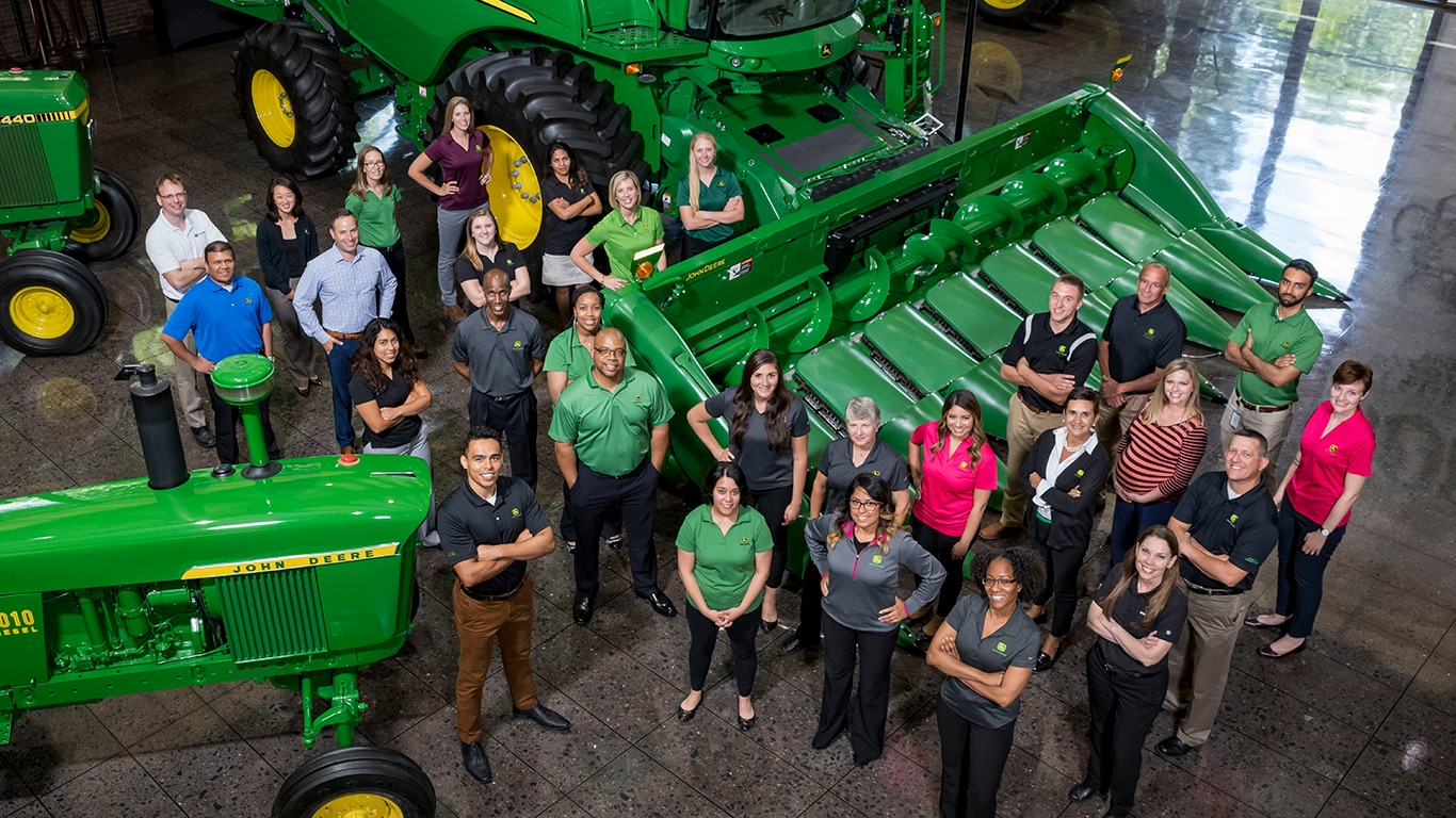 Group of employees in front of of a combine on the display floor