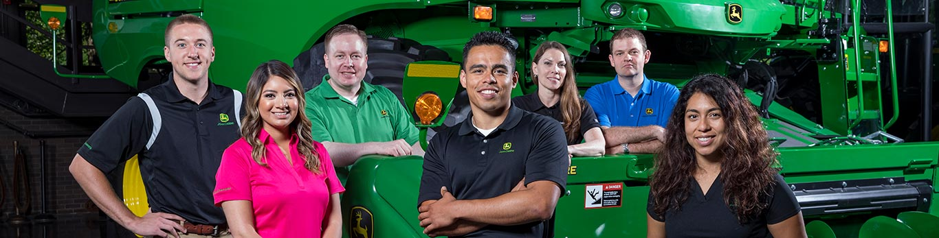 Group of employees standing with a John Deere combine