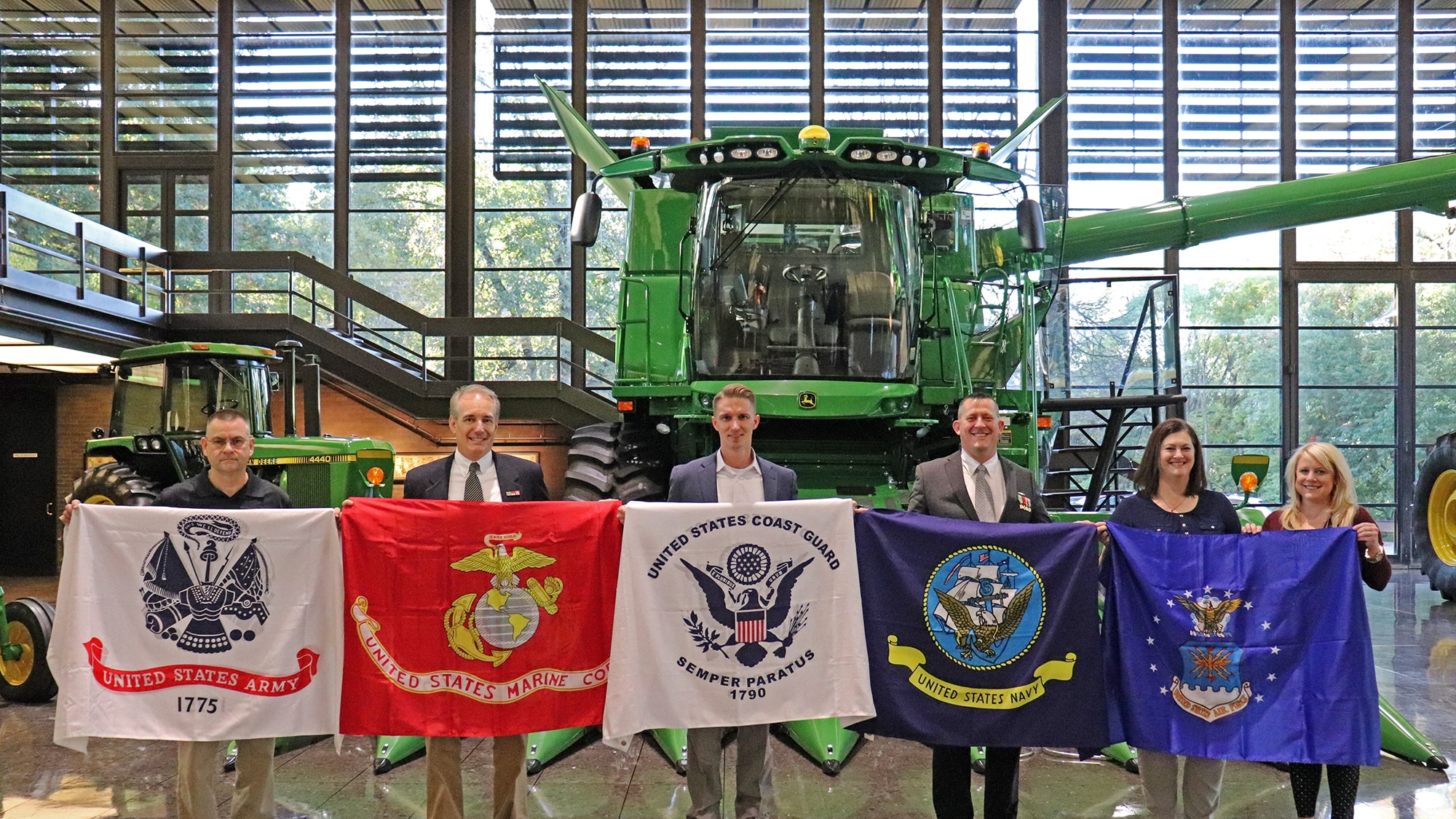 Group of employees who are Veterans holding military branch flags in front of a combine