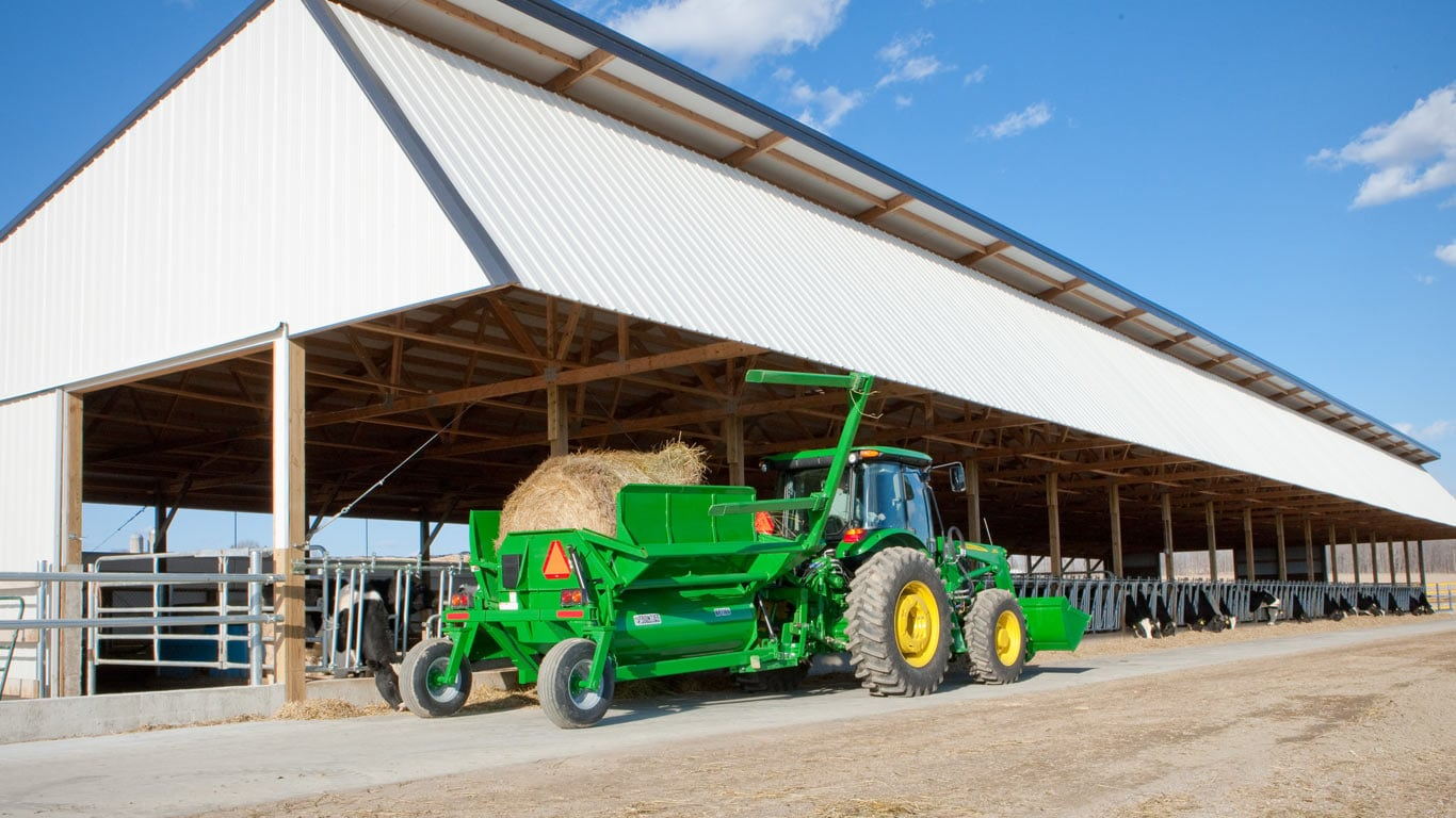 Tractor with livestock attachments in front of stalls