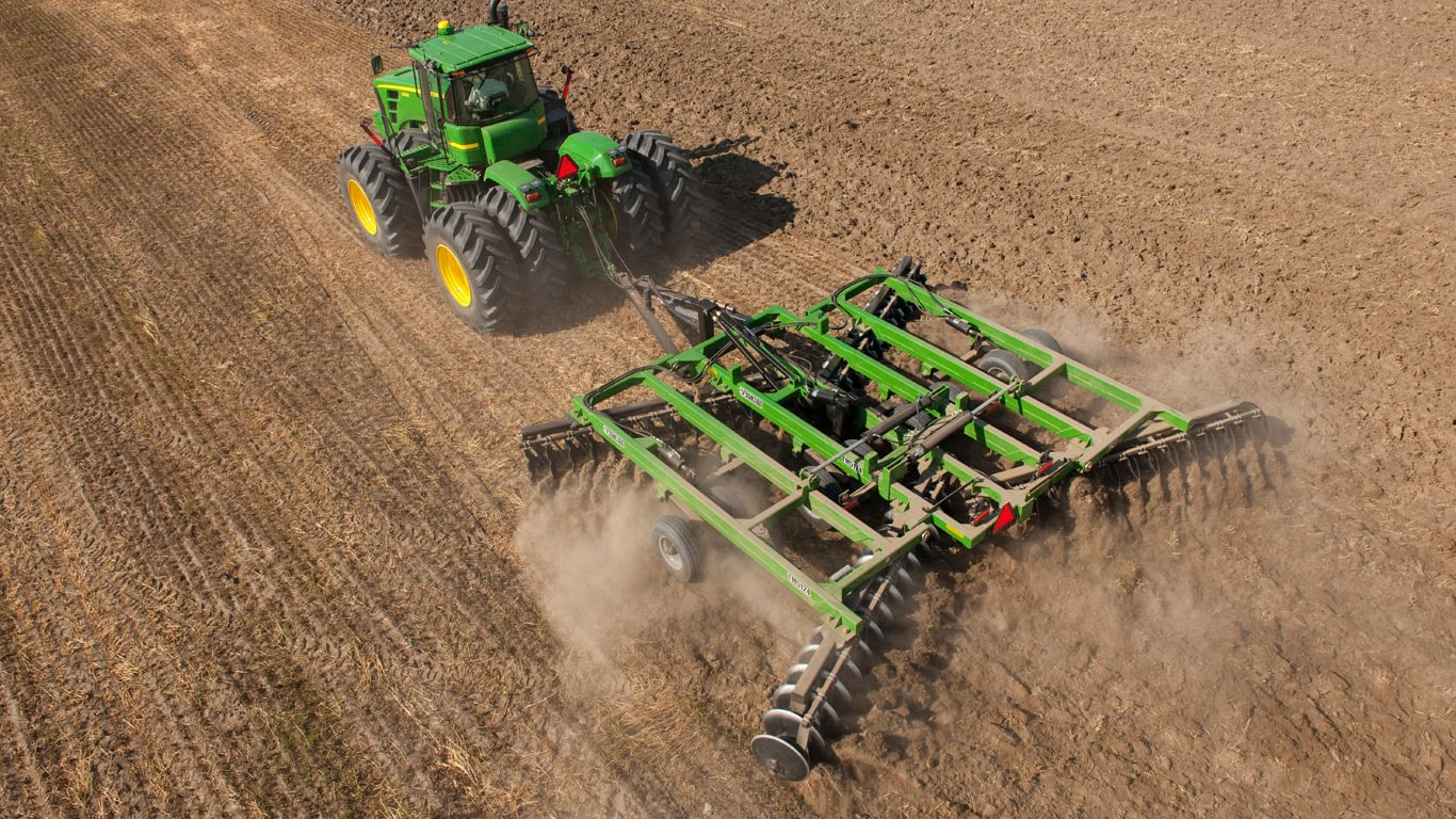 aerial view of tractor pulling tillage attachment in field