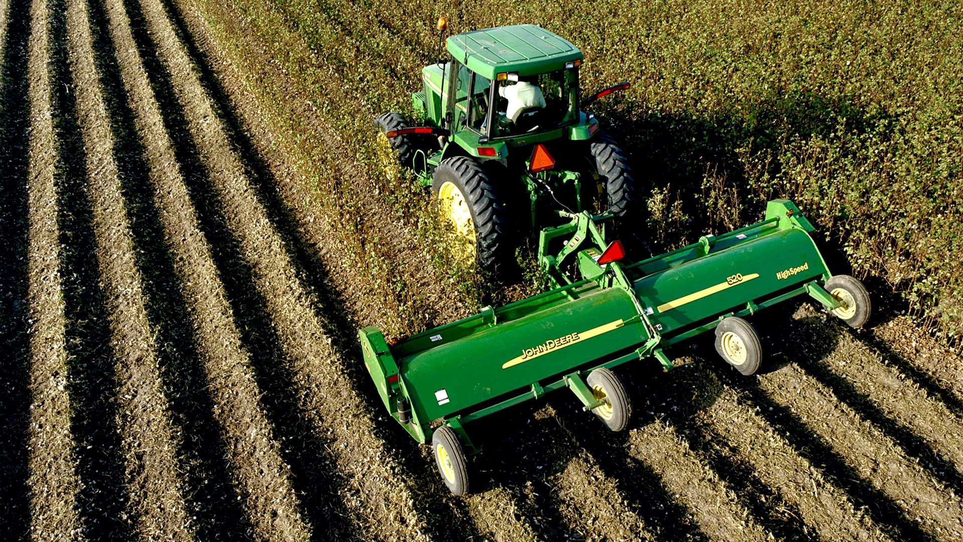aerial view of flail mower attached to tractor in a field