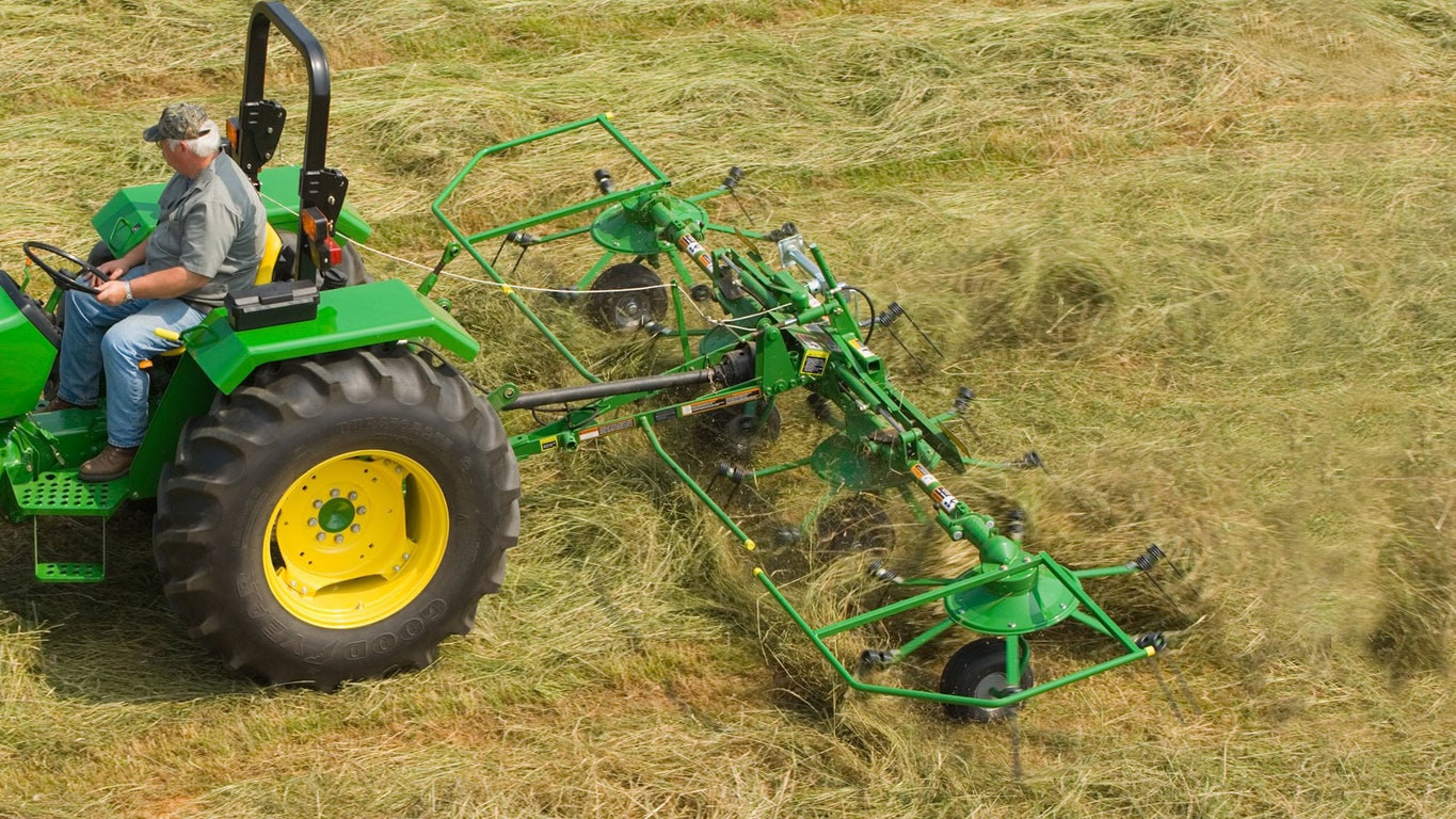 field image of Frontier™ td13 hay tedder attached to a tractor