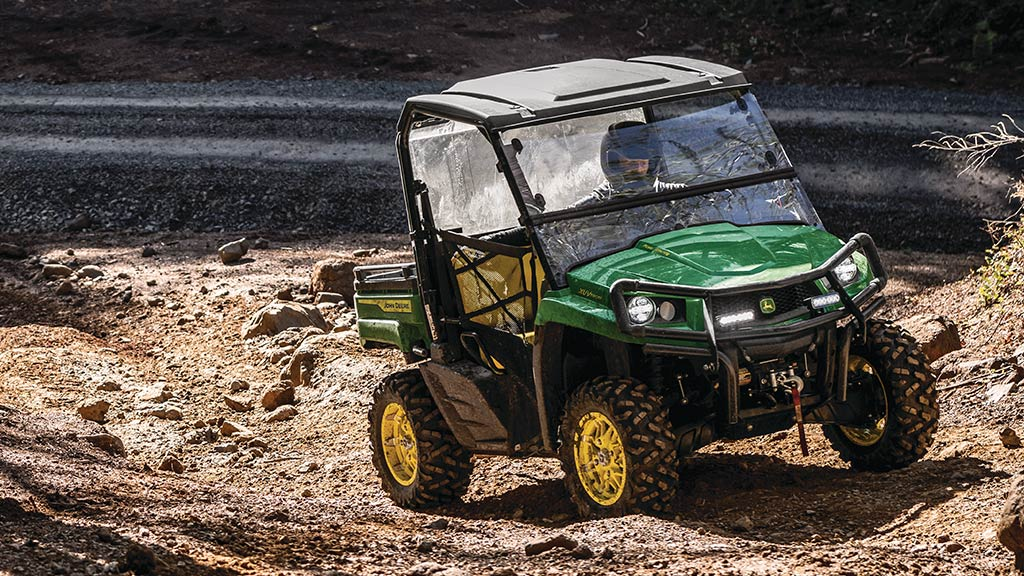 mid-size gator™ being driven on a dirt trail