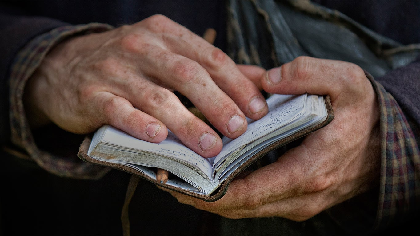 Photo of hands holding a small notebook open