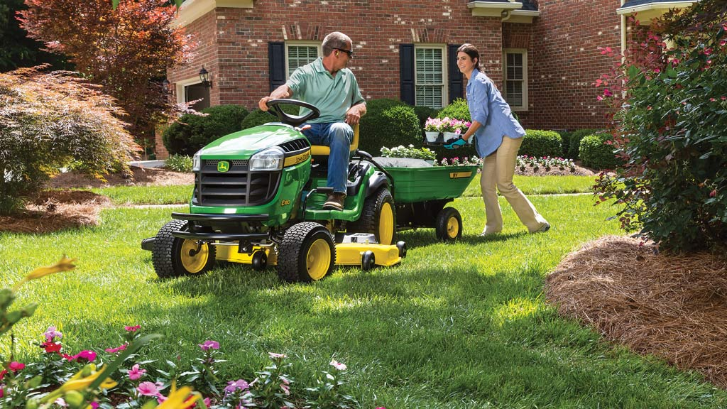 couple in yard with lawn tractor