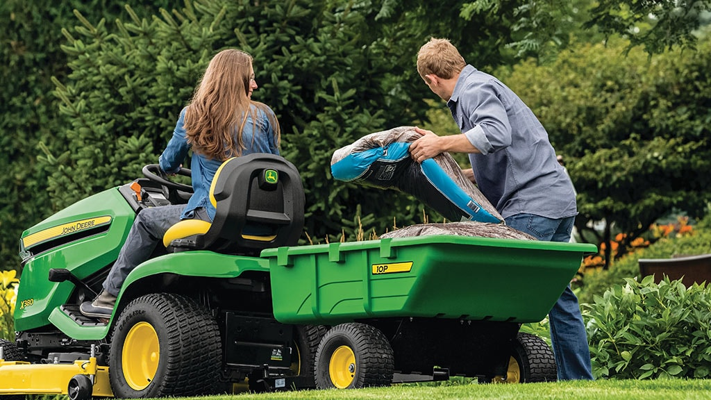 woman on a X300 lawn mower with man unloading top soil bags from cart