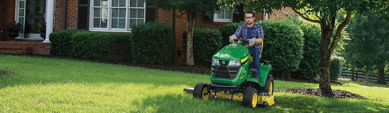 man driving x300 series lawn tractor in yard